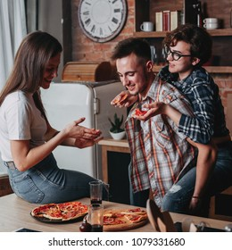 Young people having fun at home party, eating pizza and smiling. Friendship, togetherness, lifestyle, people and eating concept