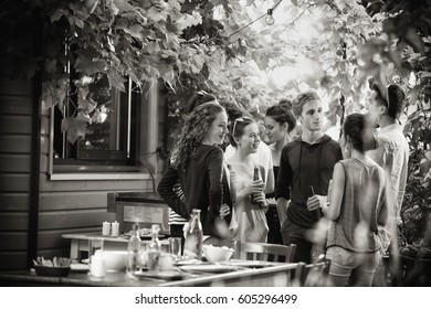 Young people having fun on the terrace, drinking beers and chatting while their friends roast the meat on the bbq. Black and white picture