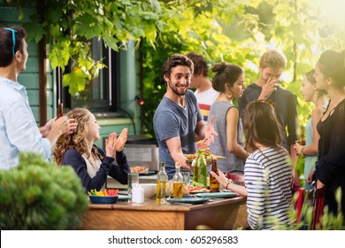 Young people having fun on the terrace, drinking beers and chatting while their friends serve the meat roasted on the bbq. Shot with flare
