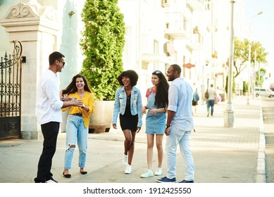Young people having fun outdoors. A group of multi-ethnic friends are talking and laughing while standing in the street