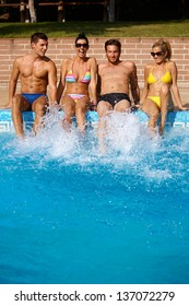 Young people having fun in swimming pool on summer holiday, smiling.