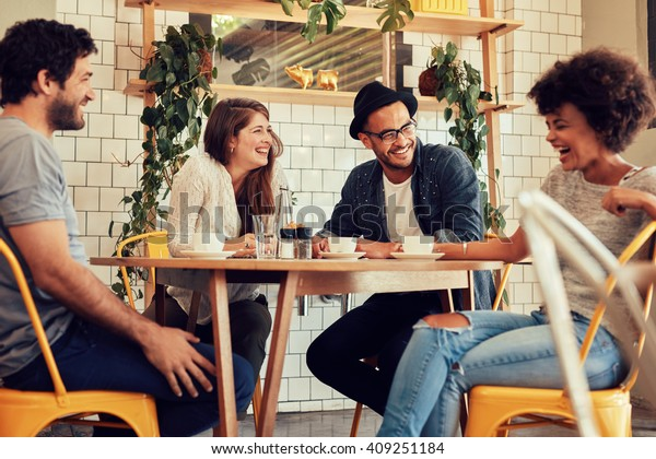Young people having a great time in cafe. Friends smiling and sitting in a coffee shop, drinking coffee and enjoying together.