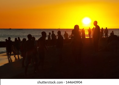 Young people having party on the beach during the sunset