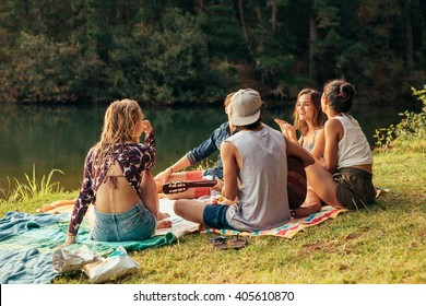 Young people having picnic near a lake. Young friends relaxing by a lake.