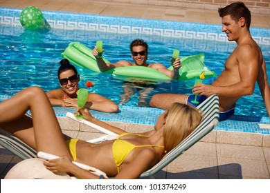 Young people having summer fun in outdoor pool.