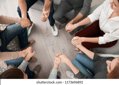 Young people holding hands together during group therapy, indoors