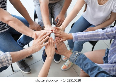 Young people holding hands together at group therapy session