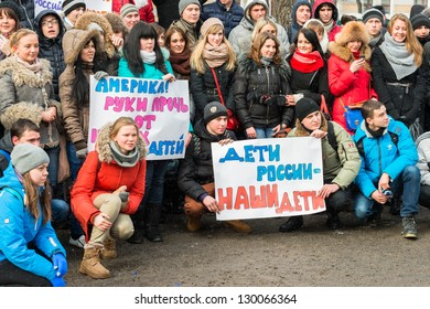 Young people holding posters with text 'America! Hands off of our children' and 'Children of Russia - our children'. Rally in support of U.S. adoption ban. Moscow, March 2, 2013