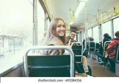 Young people inside old style tram - Happy passengers having fun inside bus - Focus on woman face - Transportation, travel and youth concept - Retro camera filter