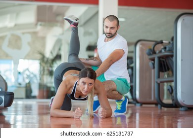 Young people involved in sports. Woman stretching with personal trainer