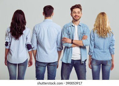 Young people in jeans on a gray background. Three are standing turned back, one man is looking at camera and smiling