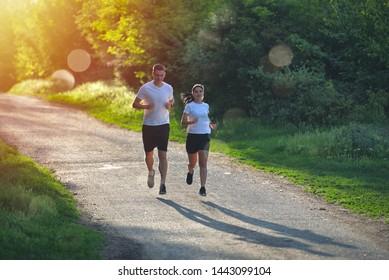 Junge Menschen joggen und trainieren in der Natur, bei Sonnenaufgang warm