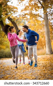 Young people jogging at the park.Female on the front.Autumn.