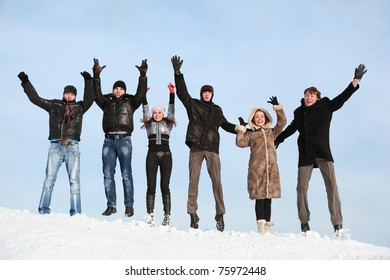 Young people jump in winter on snow and lift hands upwards