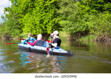 Young people are kayaking on a river in beautiful nature. Summer sunny day.
