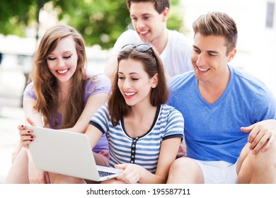 Young people with laptop outdoors