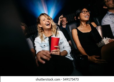 Young people laughing while watching film in movie theater. Group of friends in multiplex cinema with drinking and popcorn.