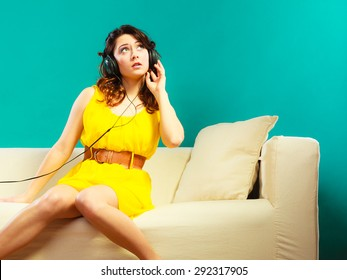 Young people leisure relax concept. Teen cute girl yellow dress in headphones listening music mp3, sitting on couch relaxing green blue background