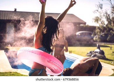 Young people lighting smoke torch on pool party on sunny day