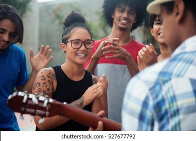 Young people listening to a concert of a guitar player