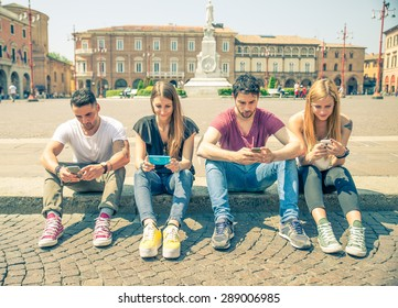 Young people looking down at cellular phone - Teenagers sitting outdoors and texting with their smartphones - Concepts about technology and global communication