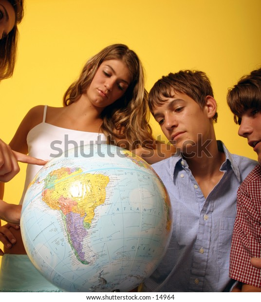 young people looking at globe