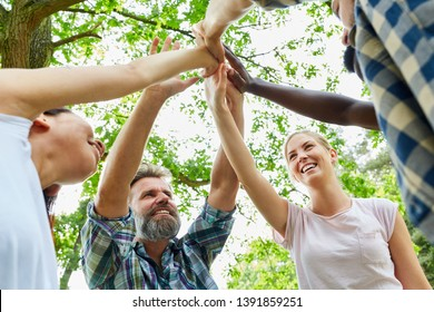 Young people make high five as a sign of teambuilding and support
