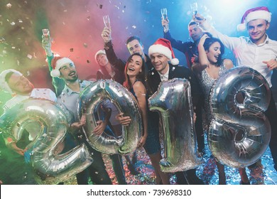 Young people at the New Year party are posing with large shiny inflatable balls in the form of numbers 2018. The guys are having fun. Behind them is a multicolored haze.