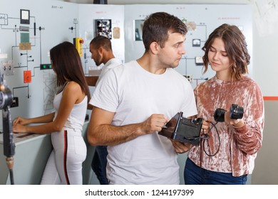 Young people with old telephone set trying to find solution of conundrum in closed space of lost room-bunker