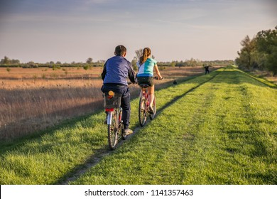 Young people on a bicycle during a bicycle tour, embankment  over the Vistula river bank near Karczew and Otwock