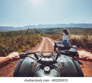 Young people on quad bikes on a countryside trail. View from a quad bike with woman driving an ATV in front on a sunny day.