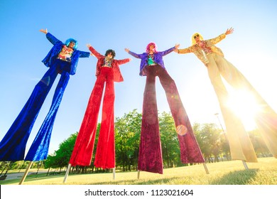 Young people on stilts posing against the blue sky.