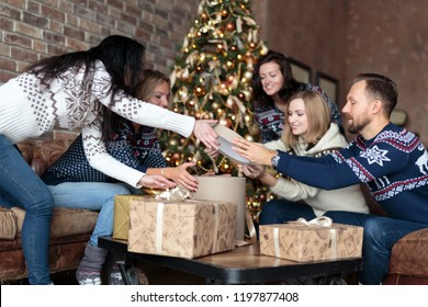 Young people opening Christmas gift boxes by a Christmas tree in cozy loft in winter