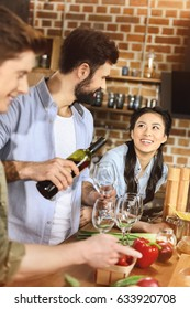 young people partying, eating and drinking wine at home party
