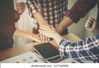 Young people placing hand together for team unity concept