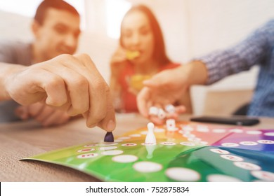 Young people play a board game using a dice and chips. On the table they have glasses with alcoholic drinks. They have fun playing a game.