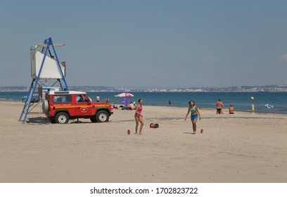 Young people play on the beach at noon, Camargue, France, 13 July 2018. A lifeguard on the tower watches people swimming.
