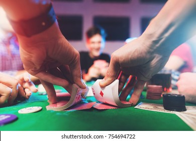 Young people play poker at the table. On the table they have glasses with alcoholic beverages, mobile phones and chips for the game. They have fun playing a game.