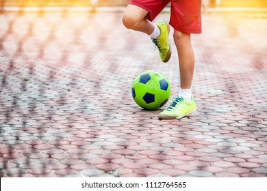 Young people playing football in street field.
