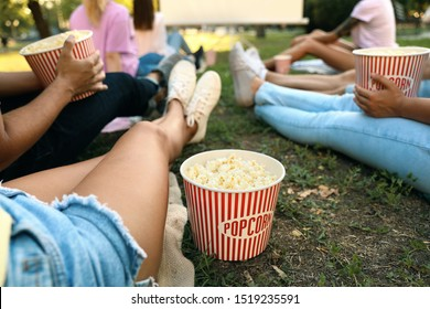 Young people with popcorn watching movie in open air cinema, closeup