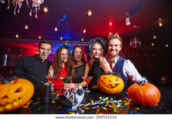 Young people posing in Halloween hats and with pumpkins