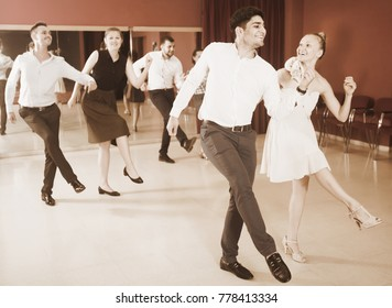 Young people practicing vigorous jive movements in dance class