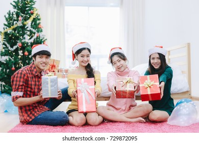 Young people are preparing christmas gift box and christmas decoration with christmas tree at home in morning.