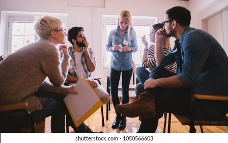 Young people with problems listening to their nervous female friend confession with shock reaction while sitting together on special group therapy.