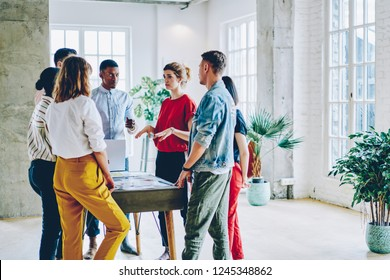 Young people professionals dressed in casual wear discussing strategy plan of collaboration standing at table with laptop in moder office.Team of hipster guys discussing cooperation on design project