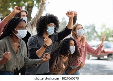 Young people in protective masks attending demonstration on the street. Emotional international group of students wearing face masks, fighting again discrimination , showing clenched fists, copy space