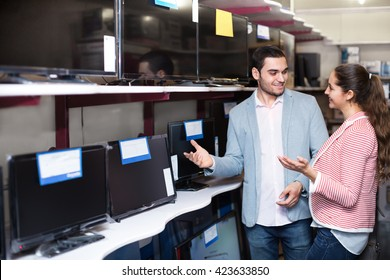 Young people purchasing a flat screen television set at electronics store