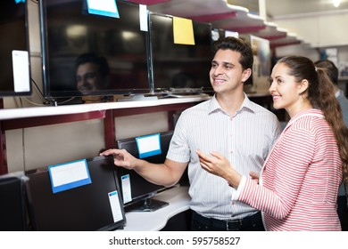 Young people purchasing flat screen television set at the electronics store