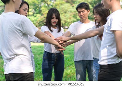 Young people putting hands together. Friends with stack of hands showing unity and teamwork.