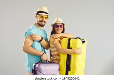 Young people ready for safe summer holiday journey. Studio portrait of happy couple holding travel cases, smiling and showing arms after receiving COVID-19 vaccine. Coronavirus vaccination concept - Shutterstock ID 1945250641